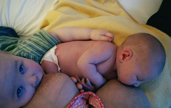 Tandemamning. Bebis och större syskon ammar samtidigt. Det större syskonet håller sin arm om ryggen på bebisen.