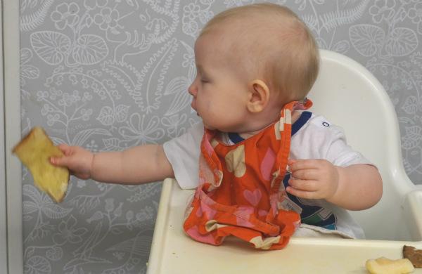 Barn i barnstol i köket håller en brödbit utanför stolen.