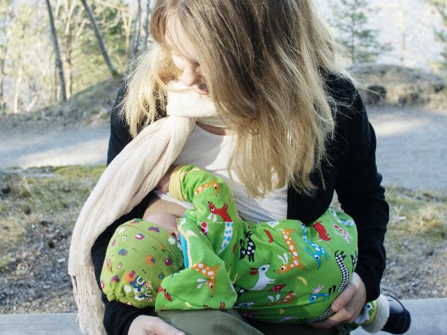 Bildserie: Amma i trikåsjal. Bebis ligger ned i famnen och ammar utomhus, vår.