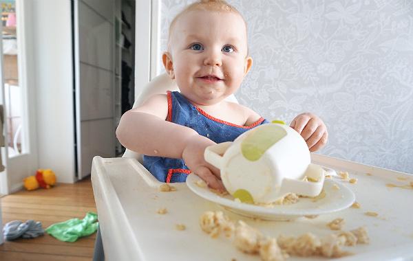 Glad bebis vid matstol, kladdar med mat och drickmugg.