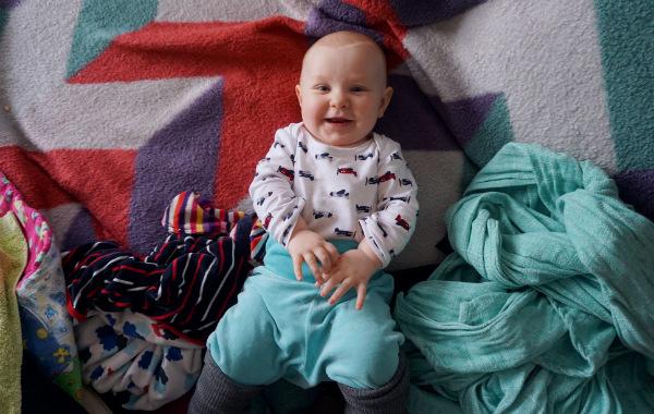 Amma max 15 minuter per bröst. Skrattande bebis på rygg på säng.
