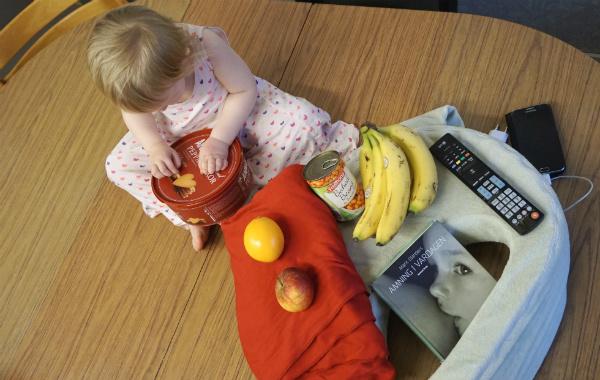 Amingsprylar. Barn på bord med amningskudde, mat, bärsjal och bok.