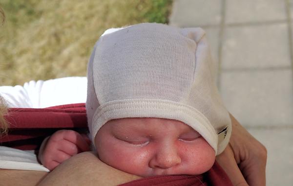 Amma i trikåsjal, liten bebis ammar utomhus.