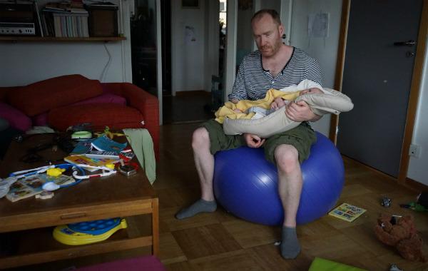Amningsbildextra. Man vaggar bebis i babynest på pilatesboll i vardagsrum.