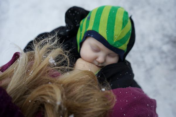 Matintroduktion. Bebis ammar utomhus, i snö, under mammans jacka.