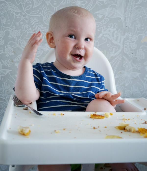 Matintroduktion, BLW. Bebis äter själv i sin matstol och ser glad ut.
